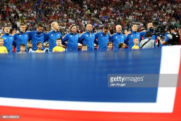 The Iceland team are seen singing their national anthem from behind an Iceland flag prior to the 2018 FIFA World Cup Russia group D match between...