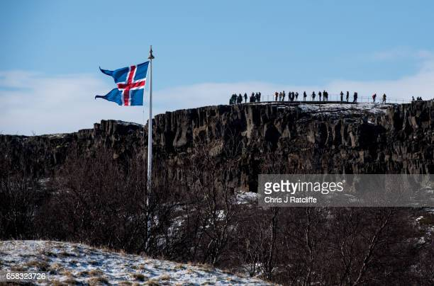 The Icelandic national flag flies in the foreground as tourists stand on top of a tectonic plate rift on March 27 2017 at Pingvellir Iceland...