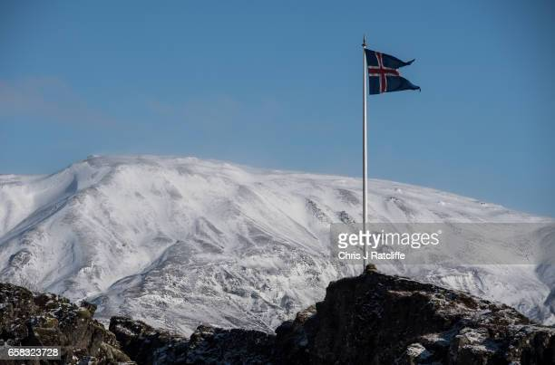 MARCH 27 The Icelandic national flag flies on top of a tectonic plate rift on March 27 2017 at Pingvellir Iceland Iceland's economy has been booming...