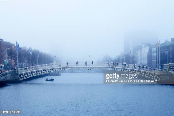the iconic ha'penny bridge with people crossing the river liffey on a foggy dublin morning - city life stock pictures, royalty-free photos & images