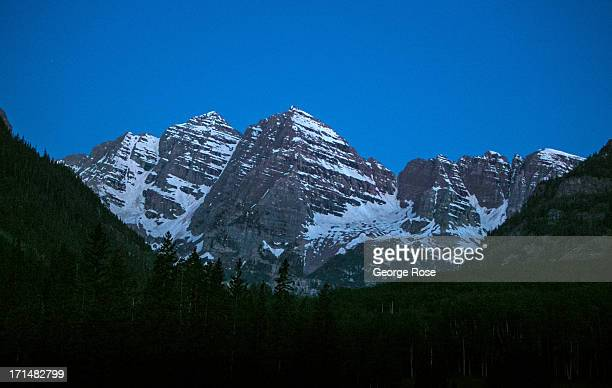 The iconic Maroon Bells are cast in a deep blue about an before sunrise on June 14 near Aspen Colorado Colorado's Rocky Mountains are part of a range...