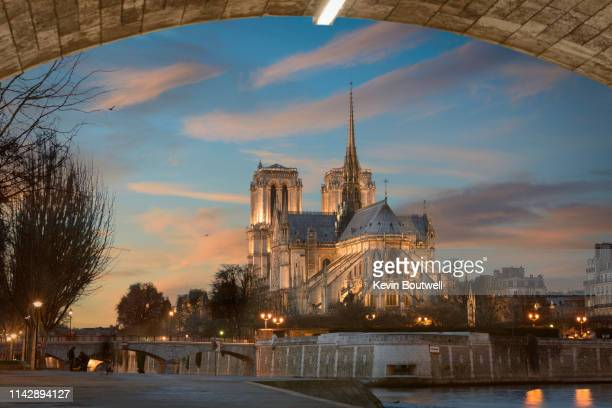 the iconic notre dame cathedral rises above the seine - notre dame de paris photos et images de collection