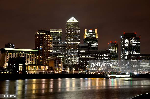 The iconic skyline and skyscrapers of London's business and financial district Canary Wharf is illuminated at night. The lights are reflected in the...