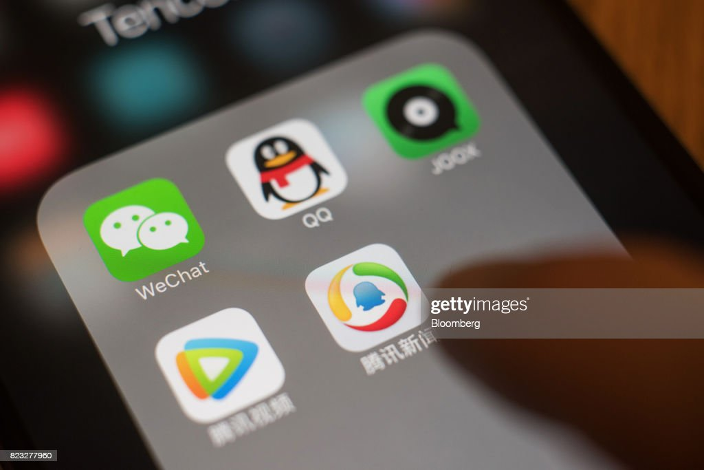 The icons for Tencent Holdings Ltd. applications WeChat, clockwise from top left, QQ, JOOX, Tencent News and Tencent Video are arranged for a photograph on an Apple Inc. iPhone taken in Hong Kong, China, on Wednesday, July 26, 2017. Tencent is scheduled to release second-quarter earnings figures on Aug 16. Photographer: Anthony Kwan/Bloomberg via Getty Images