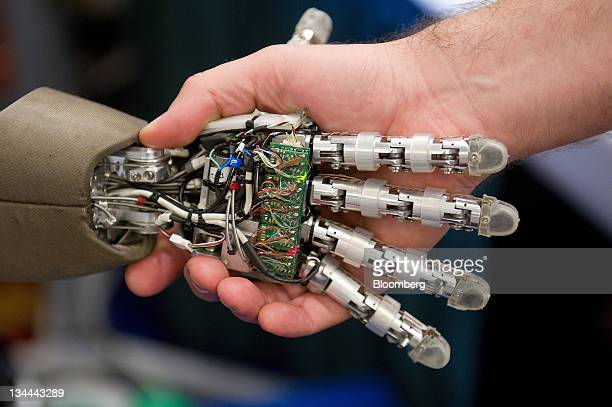 The iCub robot made at the Istituto Italiano Di Tecnologia in Genova Italy shakes hands with an attendee during the International Conference on...