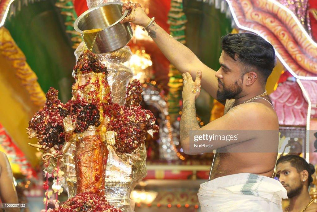 The idol of Lord Murgan is covered with pomegranate seeds and bathed