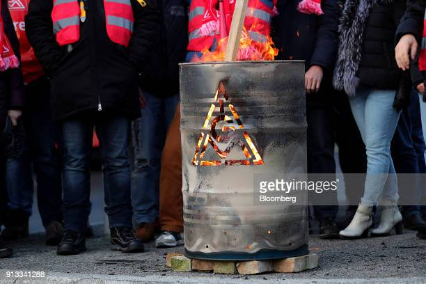 The IG Metall logo sits on a burning brazier barrel during a 24 hour strike called by the labor union outside the BMW Motorrad motorcycle factory...