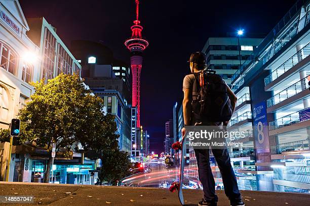the illuminated auckland sky tower during a colorful evening sunset - auckland stock pictures, royalty-free photos & images