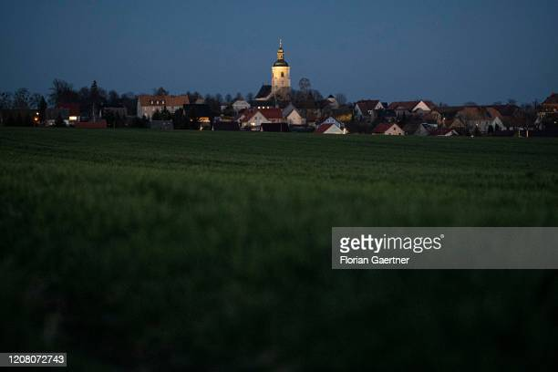 The illuminated church is pictured during blue hour on March 23, 2020 in Groeditz, Germany.
