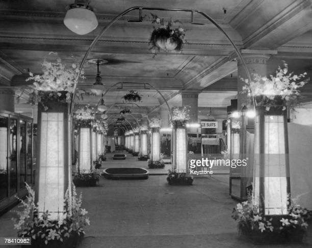 The illuminated floral aisle of Selfridges flagship store on London's Oxford Street 1934