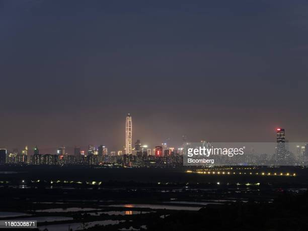 The illuminated Ping An International Finance Center , center left, and other buildings in Shenzhen stand on the horizon beyond farmland at dusk in...
