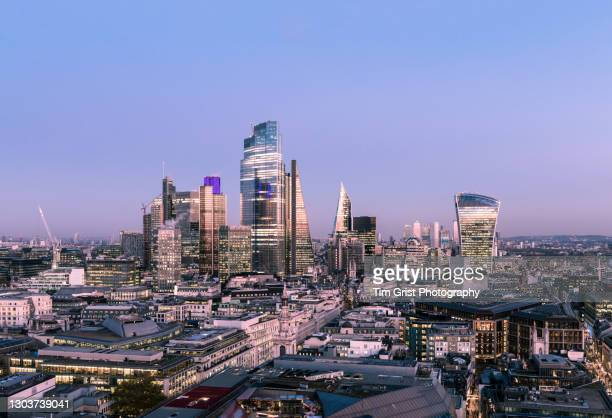 the illuminated skyline of the city of london financial district at night - economic stimulus stock pictures, royalty-free photos & images