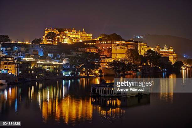 the illuminated udaipur palace complex at night - udaipur stock pictures, royalty-free photos & images