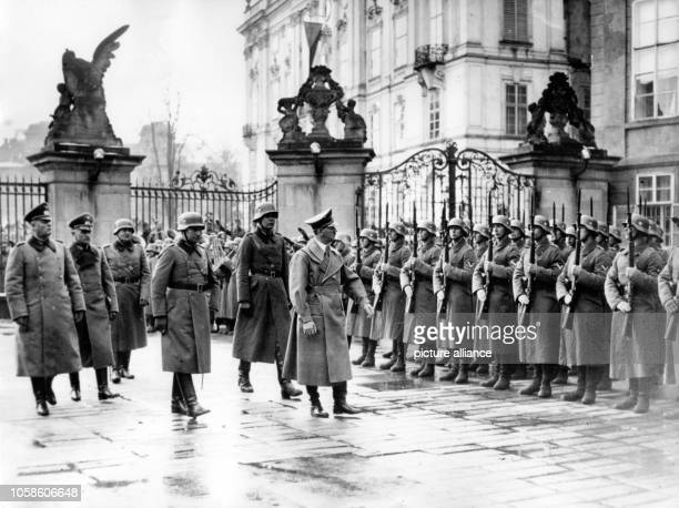 The image from the Nazi Propaganda shows Adolf Hitler marching past an honorary company in the Castle District in Prague Czech Republic after the...
