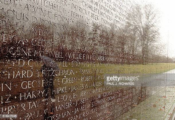 The image of an unidentified person is reflected in the Vietnam Memorial during a cloudy rainy day 28 Jan in Washington DC on the 30th anniversary of...
