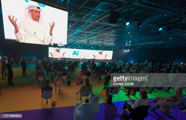 """The image of Emirati businessman Mohamed Alabba is projected on large screens as he speaks at the first """"real life"""" conference in the Gulf city of..."""