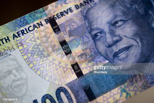 The image of former South African President Nelson Mandela sits on a 100 South African rand banknote in this arranged photograph in Pretoria, South...