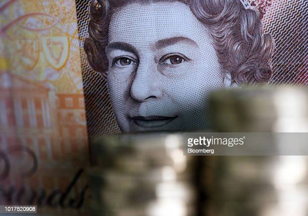 The image of Queen Elizabeth II on a British 10pound banknote looks over stacks of one pound sterling coins sit in this arranged photograph in London...