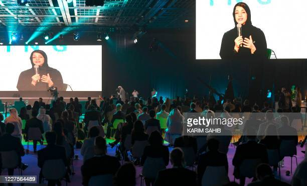 """The image of Reem al-Hashimi, UAE Minister of State for International Cooperation, is projected on large screens as she speaks at the first """"real..."""