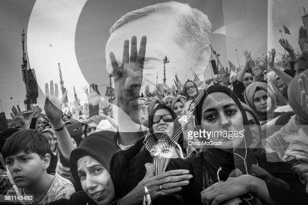 The image of Turkey's President Recep Tayyip Erdogan overlays supporters attending an AK Parti election rally on June 17 2018 in Istanbul Turkey With...