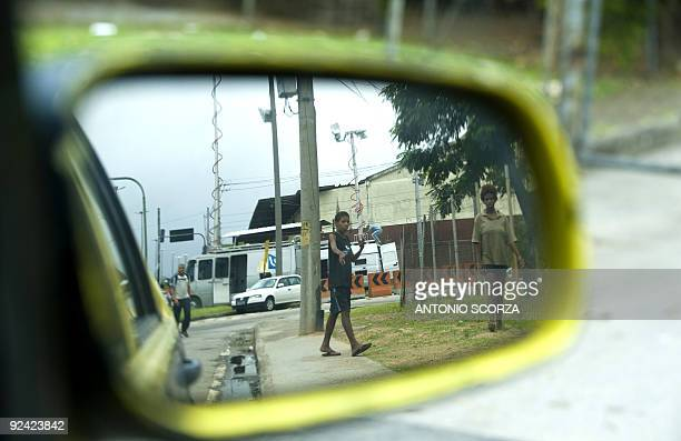 The image of two children behaving apparently under influence of drugs is reflected on a taxi's wing mirror near the Macacos shantytown in Rio de...
