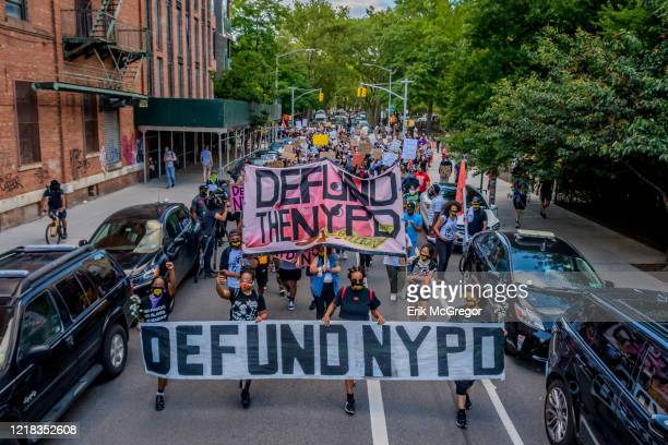 The immense crowd of protesters marching down the streets of Williamsburg behind a giant Defund NYPD banner Thousands of protesters gathered at Mc...