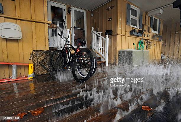 The impact of the storm effects from Hurricane Sandy which has yet to arrive in the region creates waves that pummel the belly of the decking that...