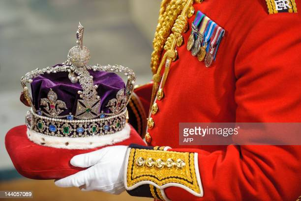 The Imperial State Crown is carried on a cushion to be presented to Britain's Queen Elizabeth II in the Palace of Westminster during the State...