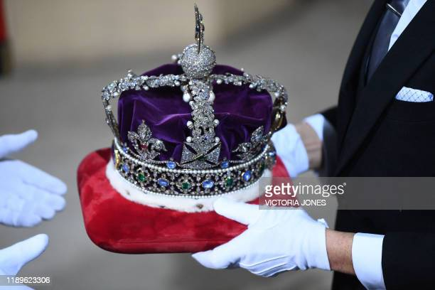 The Imperial State Crown is passed over after it arrived by car at the Sovereign's Entrance of the House of Lords for the State Opening of Parliament...