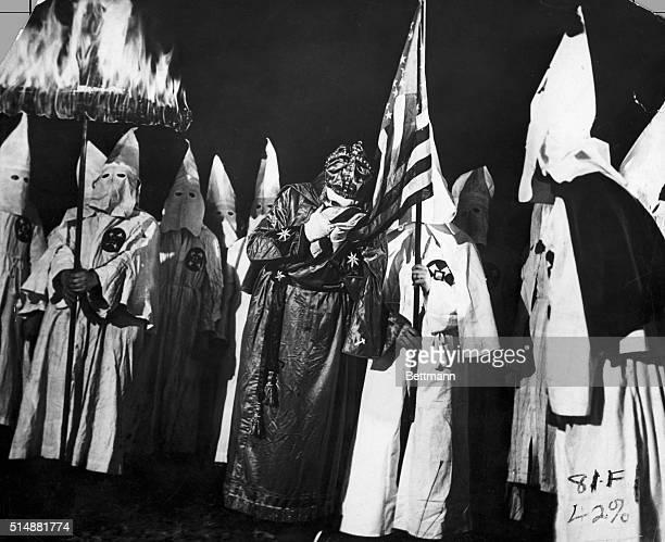 The Imperial Wizard of the Ku Klux Klan sets the example of loyalty to the US Government by kissing the flag which with the fiery cross are symbols...