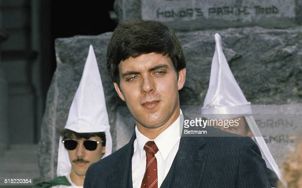 The Imperial Wizard of the National Knights of the Ku Klux Klan Don Black wearing a suit and tie with whitegowned Klan members in the background