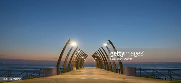 the impressive 'whale-bone' pier. early morning illumination with a budding sunrise. umhlanga rocks, durban, kwazulu natal, south africa. - ダーバン ストックフォトと画像