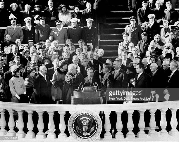 The Inaugural's most solemn moment occurs as Earl Warren Chief Justice of United States administers oath of office to John Fitzgerald Kennedy thereby...