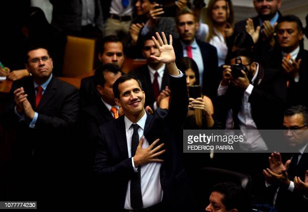 TOPSHOT The incoming president of Venezuela's National Assembly Juan Guaido waves upo arrival for the inauguration ceremony in Caracas on January 5...