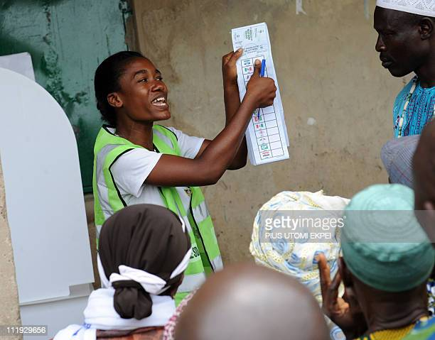 The Independent National Electoral Commission official explains the voting process to voters at a polling centre at Mowe in Ogun State Saturday April...