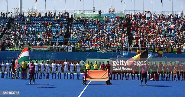The India and Belgium teams line up as the Olympic refugee flag is presented at the national anthems ceremony during the Men's hockey quarter final...