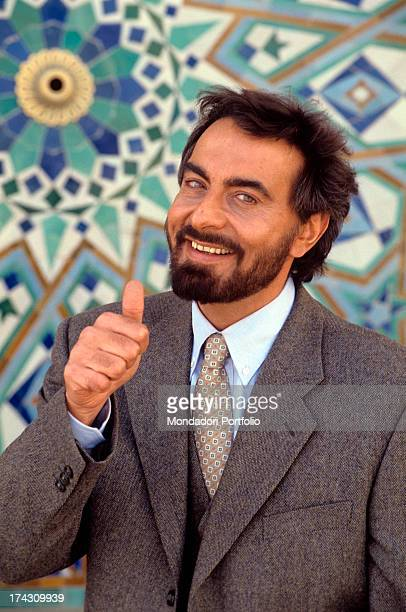 The Indian actor Kabir Bedi looks at the camera showing the thumb near the colourful tiles in the fountain of the newly built Mosque of Hassan II...