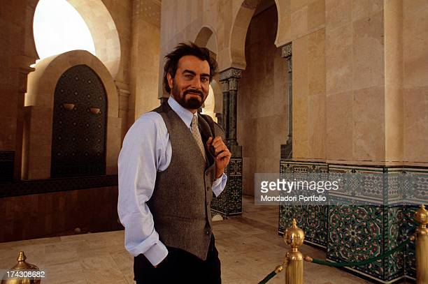 The Indian actor Kabir Bedi looks at the camera smiling with the jacket over his shoulder within the newly built Mosque of Hassan II he's in Morocco...