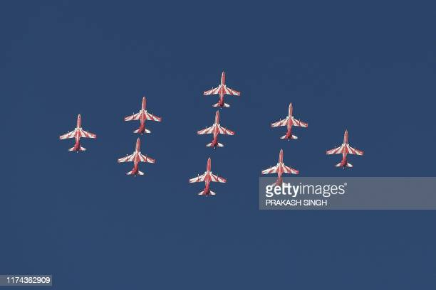 The Indian Air Force Surya Kiran aerobatic team fly past in formation during the Air Force Day parade at an IAF station in Ghaziabad on the outskirts...