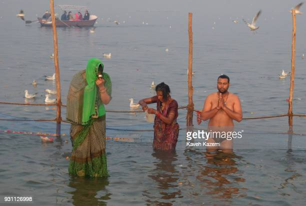The Indian Hindu devotees offer prayers at surise while taking a holy dip in Sangam which is the point of confluence of River Ganga Yamuna and...