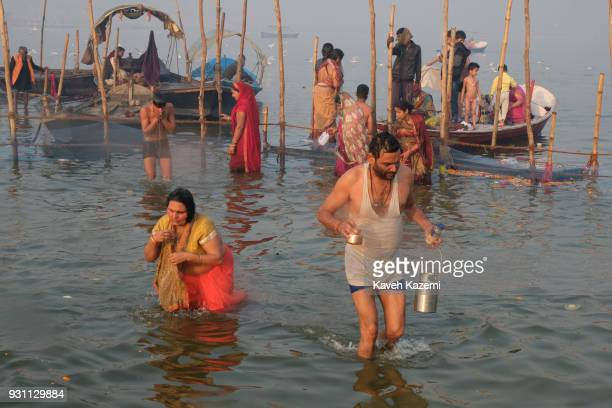 The Indian Hindu devotees offer prayers while taking a holy dip in Sangam which is the point of confluence of River Ganga Yamuna and Mythological...