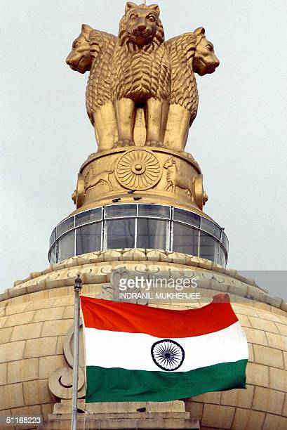The Indian national flag flies in front of the Indian national emblem lying atop the Vidhana Soudha State assembly in Bangalore 14 August 2004 on the...
