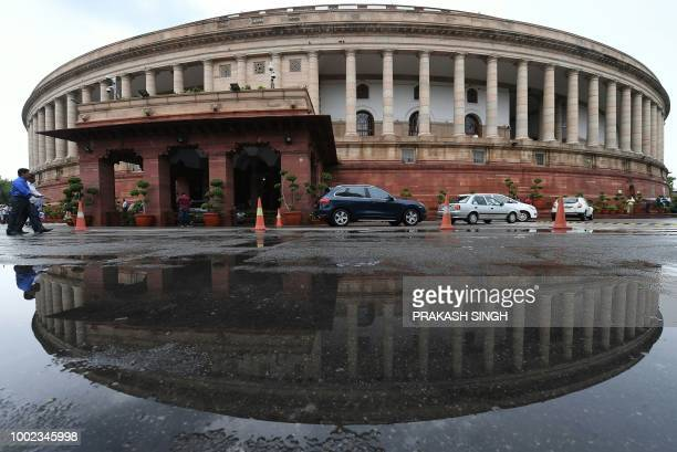 The Indian Parliament building is reflected in a puddle after heavy rain during the monsoon session of the Indian Parliament in New Delhi on July 20...