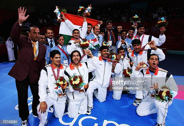 The Indian team celebrate after receiving their gold medal by defeating Pakistan in Men's Kabaddi at the 15th Asian Games Doha 2006 at Aspire Hall on...