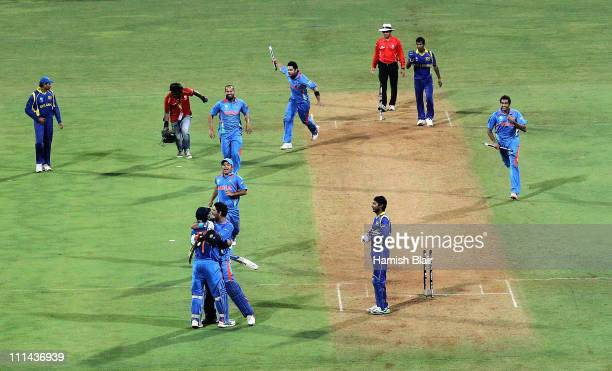The Indian team celebrate on the field after MS Dhoni hit a six to win the match during the 2011 ICC World Cup Final between India and Sri Lanka at...