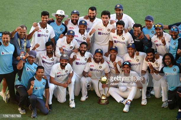 The Indian team pose with the trophy after their victory during day five of the 4th Test Match in the series between Australia and India at The Gabba...