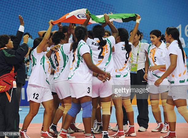 The Indian women kabaddi team celebrate with their national flag after beating Thailand in the kabaddi women's final match at the 16th Asian Games in...