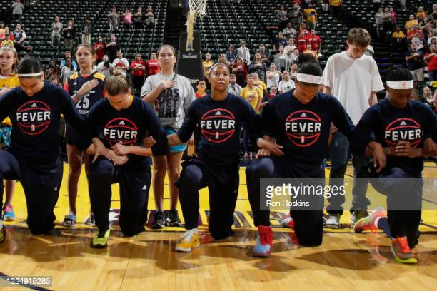 The Indiana Fever kneel during the national anthem before the game against the Phoenix Mercury during Round One of the 2016 WNBA Playoffs at Bankers...