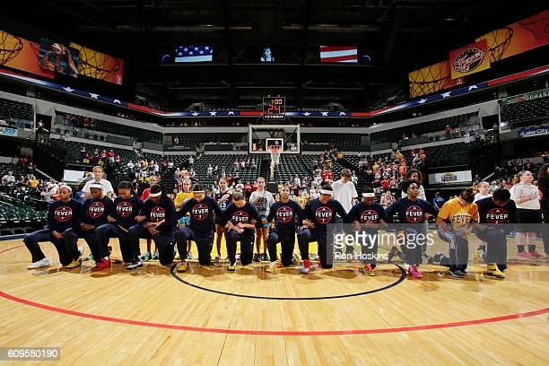 The Indiana Fever kneel during the national anthem before the game against the Phoenix Mercury during Round One of the 2016 WNBA Playoffs on...