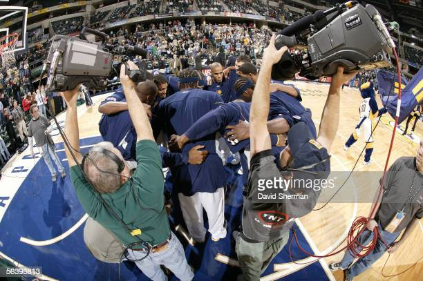 The Indiana Pacers huddle on the court near TNT TV cameramen prior to the tip off for the game against the Washington Wizards on December 8 2005 at...